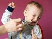 Parent spoon feeding Fussy child