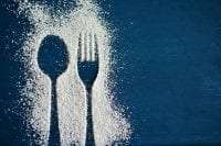 silhouette of fork and spoon on background of sugar